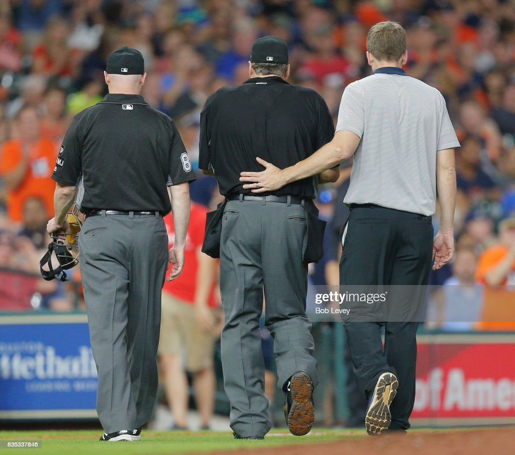 Home plate umpire Jerry Layne is escorted off the field by Houston Astros trainer Jeremiah Randle and Mike Estabrook after being hit in the left wrist by a foul pitch in the seventh inning at Minute Maid Park on August 18, 2017 in Houston, Texas.