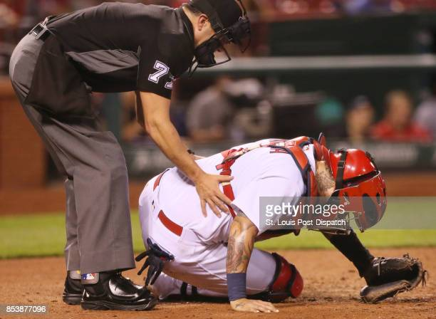 Home plate umpire Jim Reynolds tries to support St Louis Cardinals catcher Yadier Molina after Molina was hit in the head by a second consecutive...