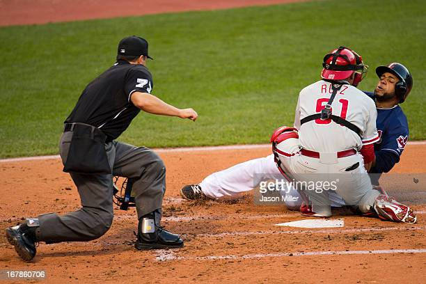 Home plate umpire Jim Reynolds watches as catcher Carlos Ruiz of the Philadelphia Phillies tries to tag Carlos Santana of the Cleveland Indians on a...
