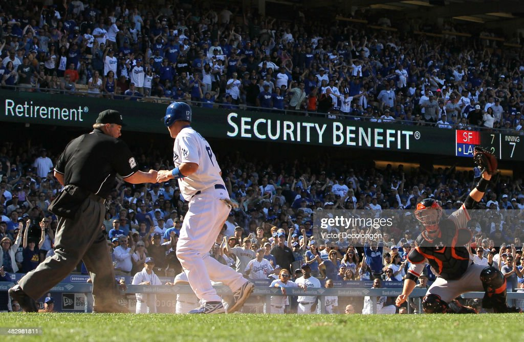 Home plate umpire Joe West calls AJ Ellis of the Los Angeles Dodgers out at the plate as catcher Buster Posey of the San Francisco Giants holds up...
