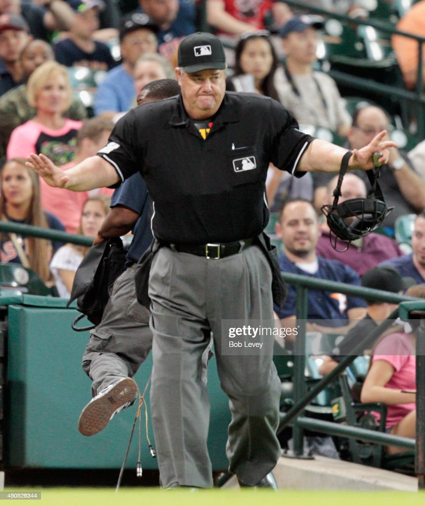 Home plate umpire Joe West signals safe after a play at third base was challenged at Minute Maid Park on June 12 2014 in Houston Texas