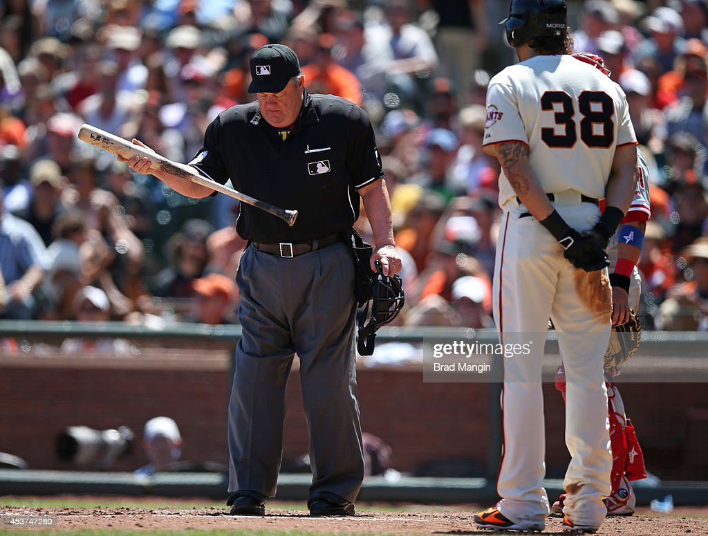 Home plate umpire Joe West uses a bat belonging to Michael Morse of the San Francisco Giants to do some grounds keeping around the home plate area...