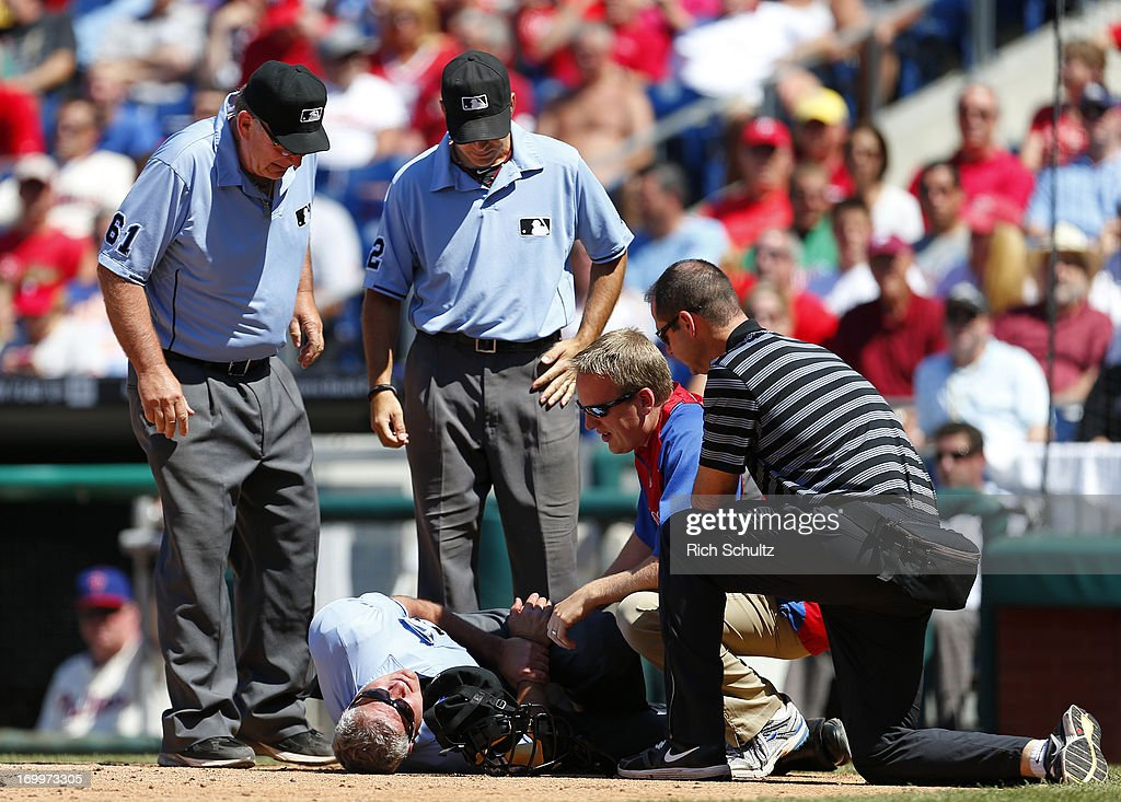 Home plate umpire John Hirschbeck #17 lies on the ground and is looked after by medical personal after being hit on the right wrist by a ball in the seventh inning of a game between the Miami Marlins and the Philadelphia Phillies on June 5, 2013 at Citizens Bank Park in Philadelphia, Pennsylvania. Looking on are umpires Bob Davidson #61 and James Hoye (92) The Phillies defeated the Marlins 6-1.