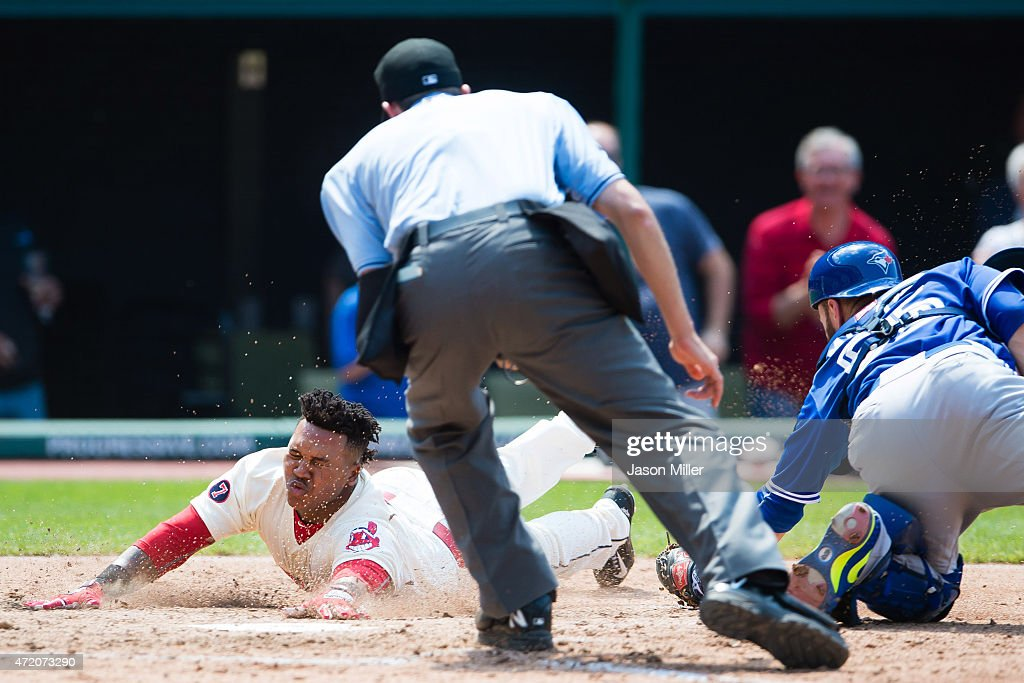 Home plate umpire John Tumpane #74 watches as catcher Russell Martin #55 of the Toronto Blue Jays misses the tag as Jose Ramirez #11 of the Cleveland Indians scores on a hit by Michael Brantley #23 during the fifth inning at Progressive Field on May 3, 2015 in Cleveland, Ohio.