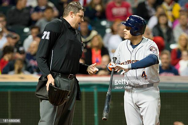 Home plate umpire Jordan Baker listens to Brandon Laird of the Houston Astros argue that he was hit by the ball on strike three during the seventh...