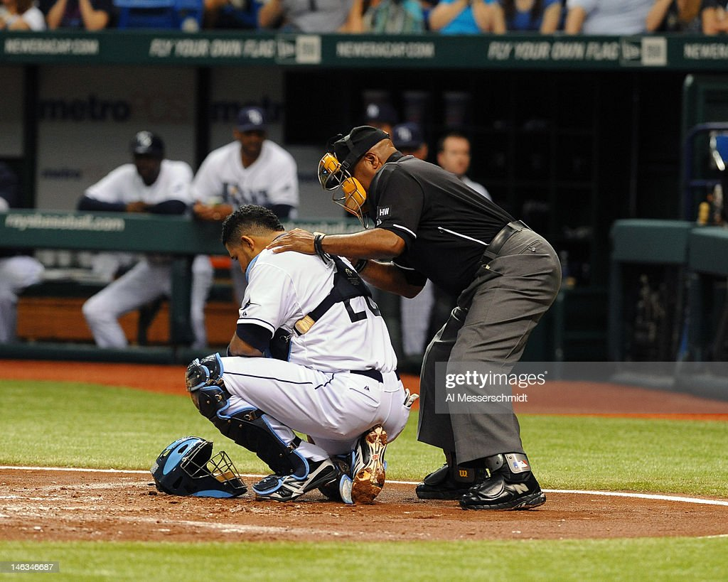 Home plate umpire Laz Diaz grabs catcher <a gi-track='captionPersonalityLinkClicked' href=/galleries/search?phrase=Jose+Molina&family=editorial&specificpeople=206365 ng-click='$event.stopPropagation()'>Jose Molina</a> #28 of the Tampa Bay Rays after Molina is hit in the mask by a foul ball against the New York Mets June 14, 2012 at Tropicana Field in St. Petersburg, Florida.