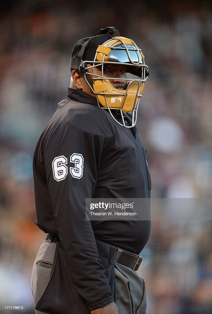 Home plate umpire Laz Diaz looks into the Miami Marlins dugout during an Major League Baseball game against the San Francisco Giants at ATT Park on...