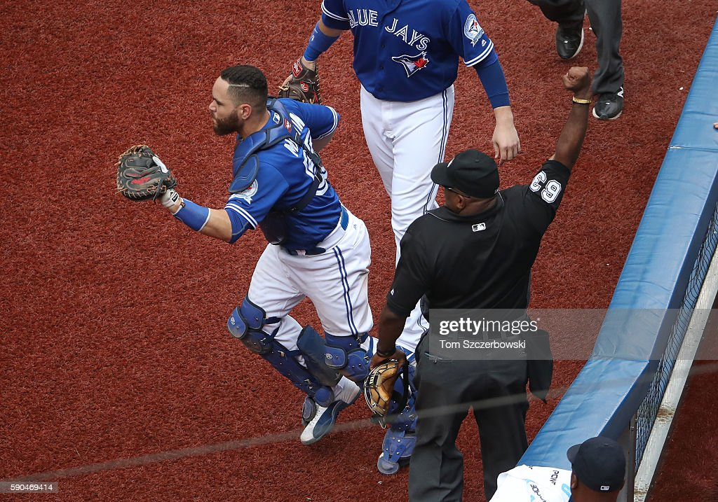Home plate umpire Laz Diaz signals an out after Russell Martin of the Toronto Blue Jays caught a foul pop by leaning over the dugout railing in the...