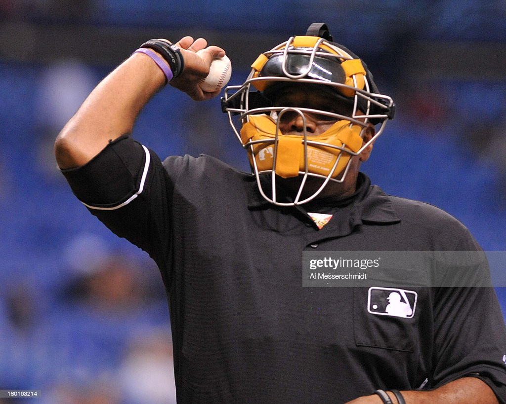 Home plate umpire Laz Diaz tosses a baseball as the Tampa Bay Rays host the Los Angeles Angels of Anaheim August 28 2013 at Tropicana Field in St...
