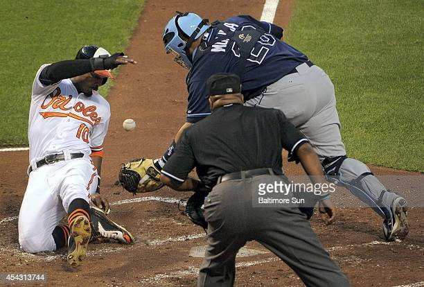 Home plate umpire Laz Diaz watches Tampa Bay Rays catcher Jose Molina get the ball too late as the Baltimore Orioles' Adam Jones blows a bubble while...