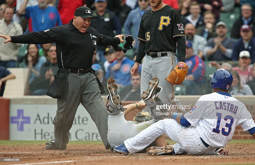Home plate umpire Mark Carlson calls safe on Starlin Castro of the Chicago Cubs as Pittsburgh Pirates catcher Tony Sanchez falls over in the fourth inning at Wrigley Field, Thursday, April 10, 2014, in Chicago. Castro scored off a Welington Castillo's hit.