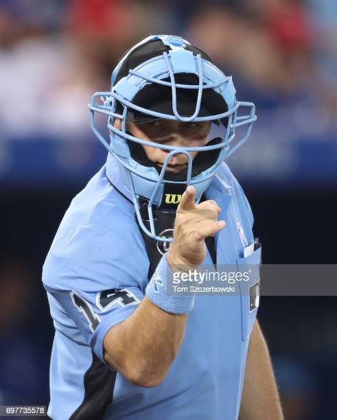 Home plate umpire Mark Wegner calls a strike while wearing a light blue mask on Fathers Day during the Toronto Blue Jays MLB game against the Chicago...
