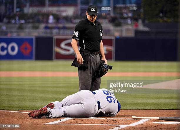 Home plate umpire Mark Wegner looks on as Yasiel Puig of the Los Angeles Dodgers lies on the ground after being hit with a pitch during the first...