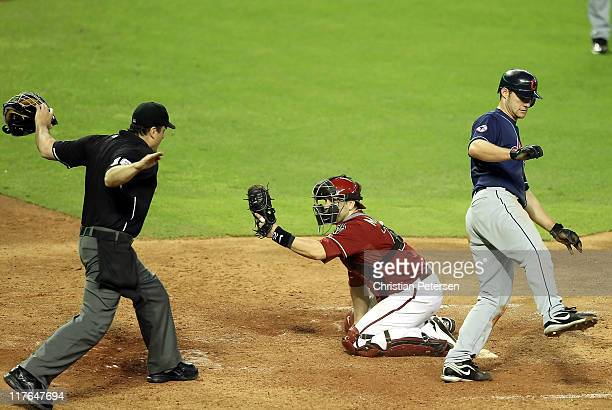 Home plate umpire Mike DiMuro calls Lou Marson of the Cleveland Indians safe as he slides in to score a run past the tag from catcher Miguel Montero...