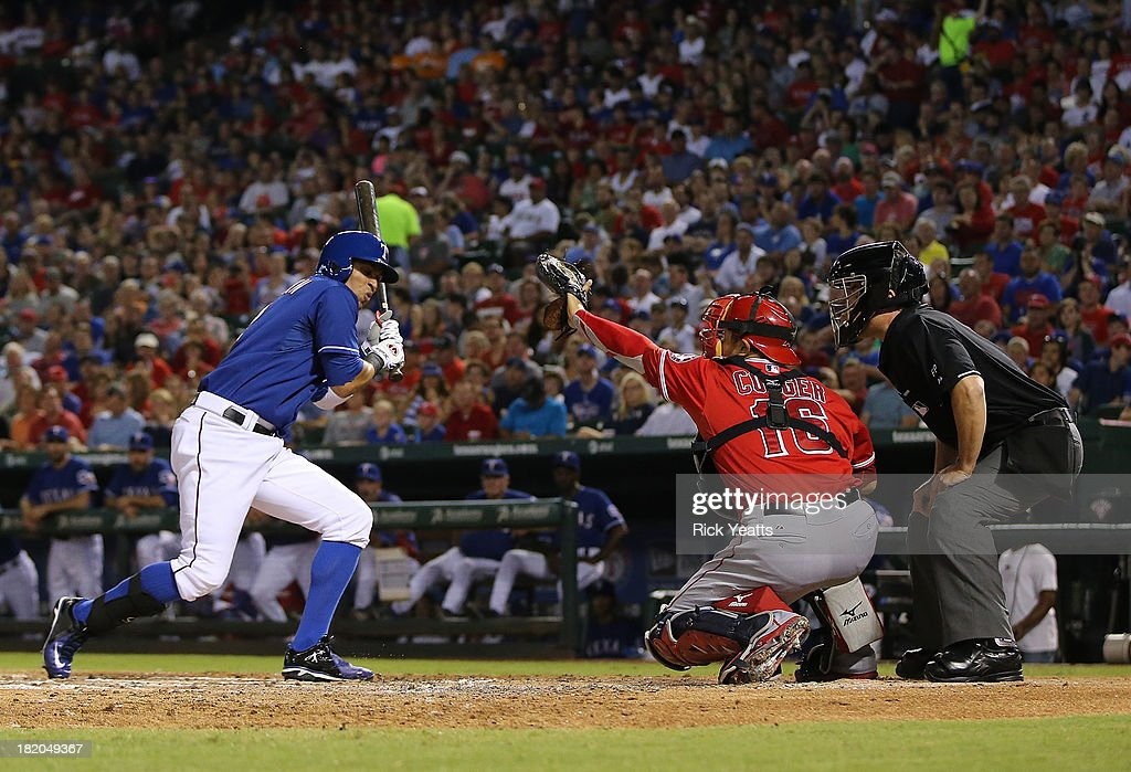 Home plate umpire Mike DiMuro #16 looks on as Leonys Martin #2 of the Texas Rangers reacts to a inside pitch and <a gi-track='captionPersonalityLinkClicked' href=/galleries/search?phrase=Hank+Conger&family=editorial&specificpeople=713039 ng-click='$event.stopPropagation()'>Hank Conger</a> #16 of the Los Angeles Angels of Anaheim makes the catch at Rangers Ballpark in Arlington on September 27, 2013 in Arlington, Texas.