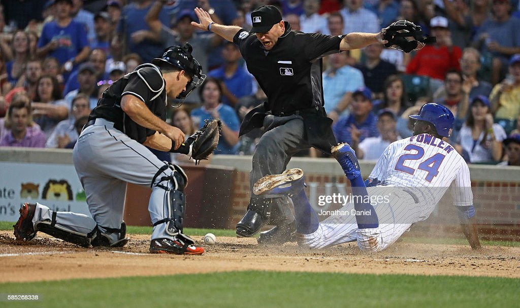 Home plate umpire Mike Muchlinski #76 signals that Dexter Fowler #24 of the Chicago Cubs is safe at home plate after J.T. Realmuto #11 of the Miami Marlins dropped the ball on the tag attempt in the 3rd inning at Wrigley Field on August 2, 2016 in Chicago, Illinois.