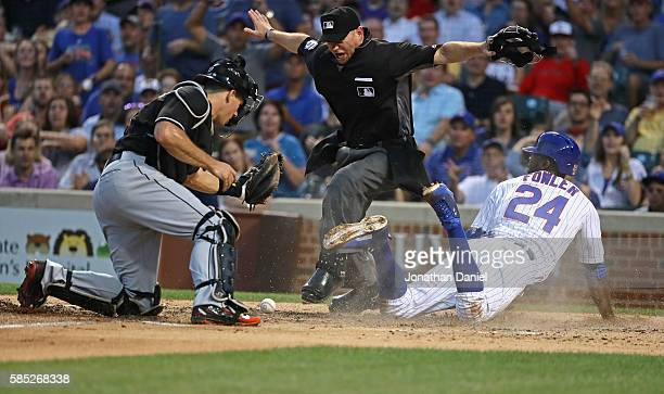 Home plate umpire Mike Muchlinski signals that Dexter Fowler of the Chicago Cubs is safe at home plate after JT Realmuto of the Miami Marlins dropped...