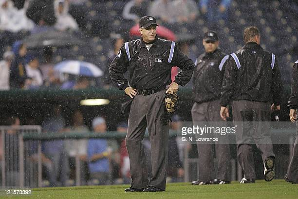 Home plate umpire Mike Reilly calls for the ground's crew to put on the tarp during the 3rd inning between the Oakland A's and Kansas City Roylas at...