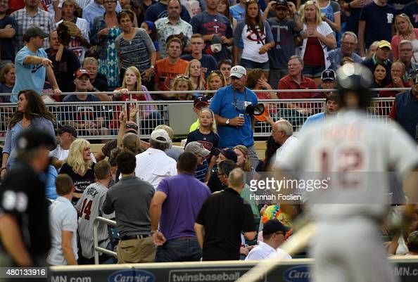 Home plate umpire Mike Winters and Anthony Gose of the Detroit Tigers look on as a fan is attended to after a foul ball hit her in the head during...