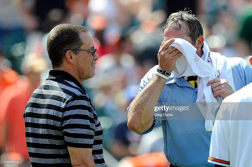 Home plate umpire Paul Nauert cools off with a wet towel from Orioles trainer Richie Bancells in the eighth inning of the game against the Toronto Blue Jays at Oriole Park at Camden Yards on July 14, 2013 in Baltimore, Maryland.