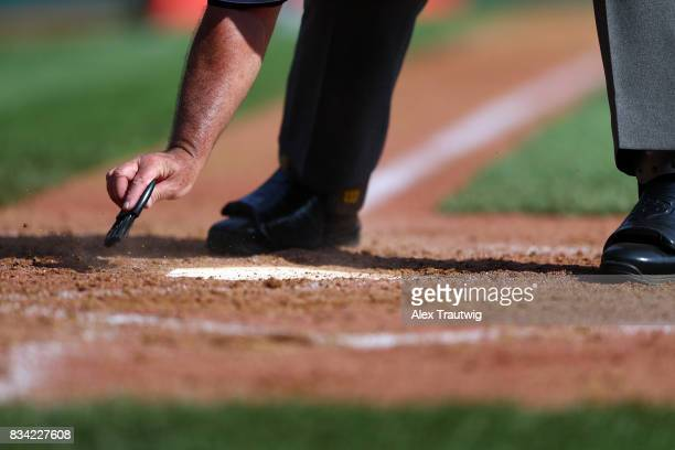 Home plate umpire Randall Kushner brushes dirt from home plate during Game 2 of the 2017 Little League World Series between the New England team from...