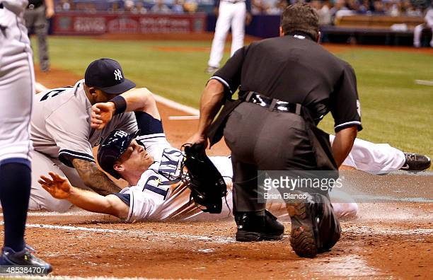 Home plate umpire Rob Drake looks on as Logan Forsythe of the Tampa Bay Rays scores in front of pitcher CC Sabathia of the New York Yankees after...