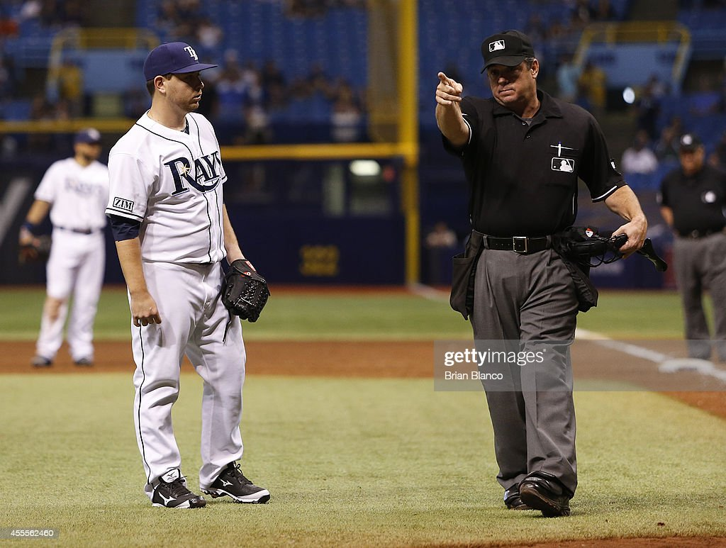 Home plate umpire Rob Drake warns the New York Yankees bench as he speaks with pitcher Steven Geltz of the Tampa Bay Rays after Geltz hit Derek Jeter...