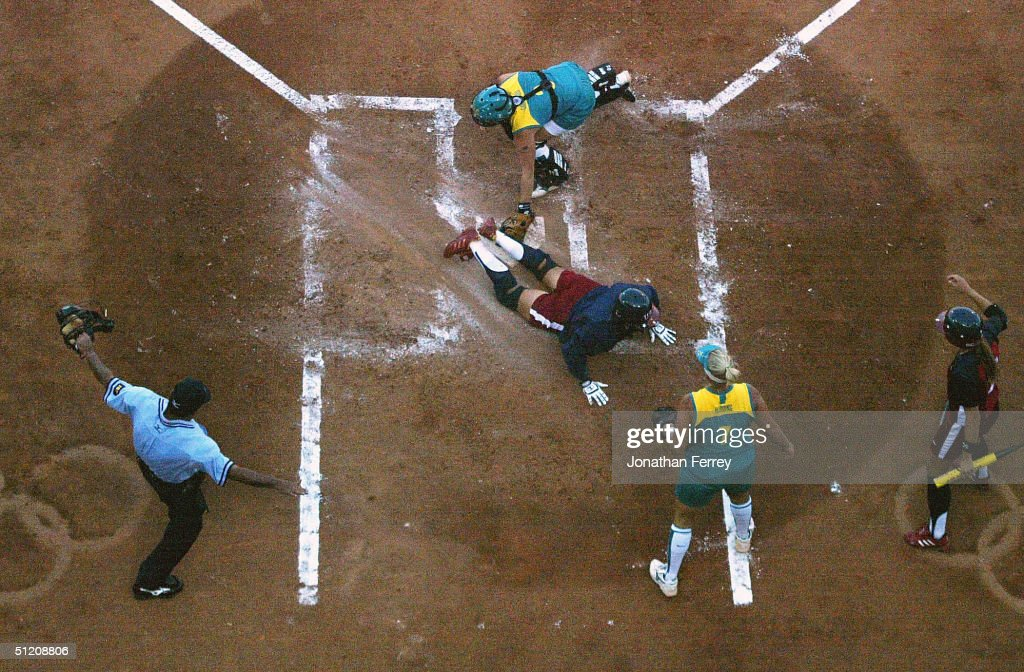 Home plate umpire Santos Vasquez gives the safe call as Lisa Fernandez of the United States scores just ahead of the tag of catcher Marissa Carpadios...
