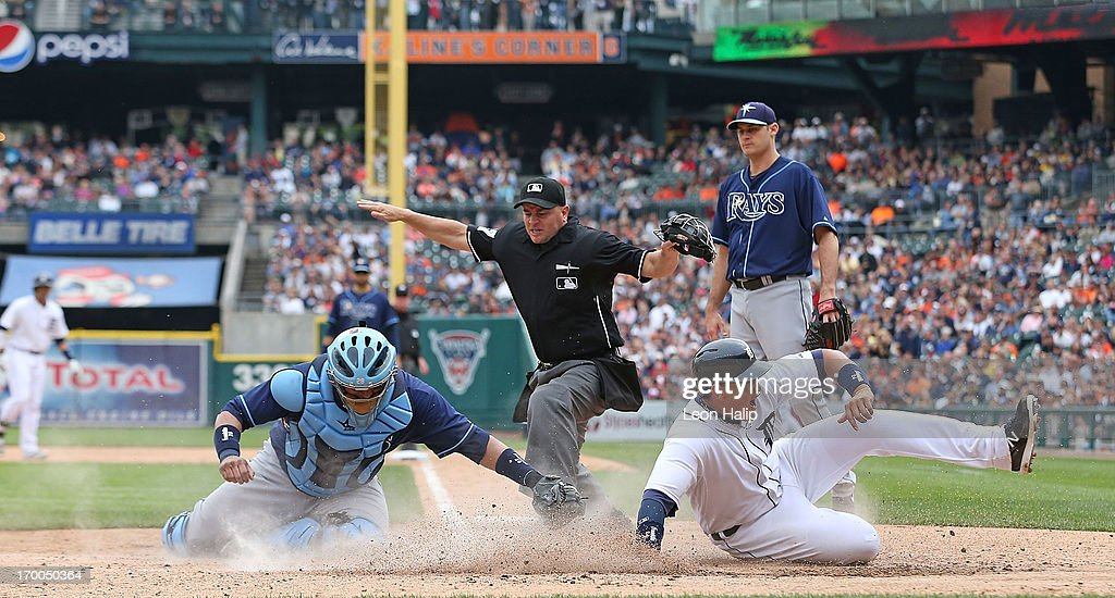 Home plate umpire Scott Barry calls Miguel Cabrera #24 of the Detroit Tigers safe at home as Jose Molina #28 of the Tampa Bay Rays attempts to make the tag at during the seventh inning of the game at Comerica Park on June 6, 2013 in Detroit, Michigan. The Tigers defeated the Rays 5-2.