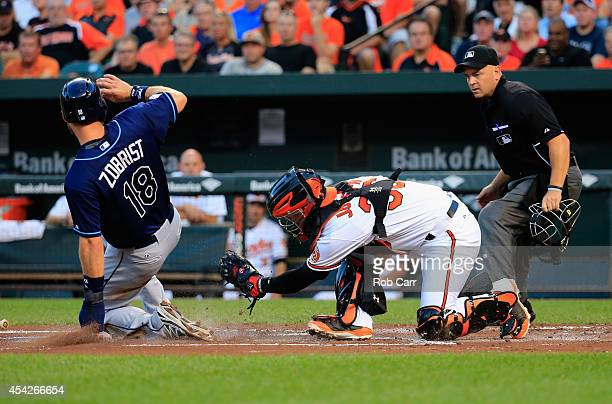 Home plate umpire Scott Barry looks on as Ben Zobrist of the Tampa Bay Rays scores a run at home plate as catcher Caleb Joseph of the Baltimore...