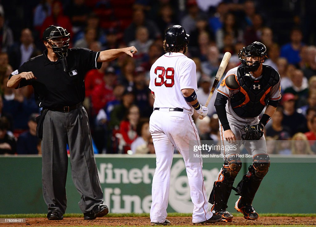 Home plate umpire Tim McClelland #36 signals the called third strike against Jarrod Saltalamacchia #39 of the Boston Red Sox that ended the game while Matt Wieters #32 heads towards the mound to celebrate on August 29, 2013 at Fenway Park in Boston Massachusetts.