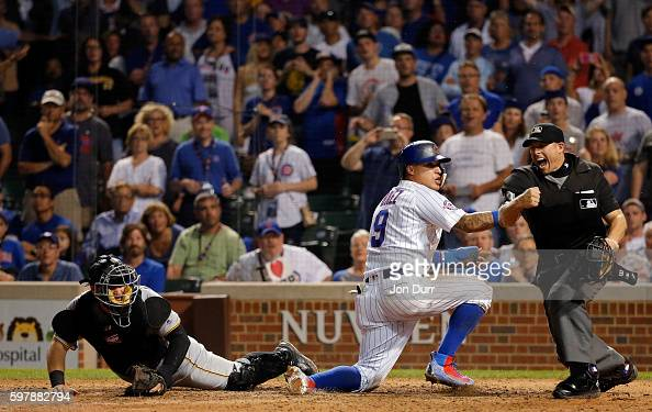 Home plate umpire Tripp Gibson calls Javier Baez of the Chicago Cubs out after being tagged by Francisco Cervelli of the Pittsburgh Pirates for the...
