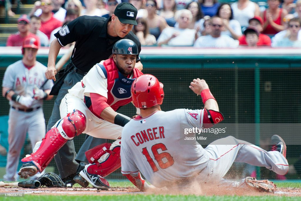 Home plate umpire Vic Carapazza #85 watches as catcher Carlos Santana #41 of the Cleveland Indians tags out <a gi-track='captionPersonalityLinkClicked' href=/galleries/search?phrase=Hank+Conger&family=editorial&specificpeople=713039 ng-click='$event.stopPropagation()'>Hank Conger</a> #16 of the Los Angeles Angels of Anaheim during the second inning at Progressive Field on August 11, 2013 in Cleveland, Ohio.