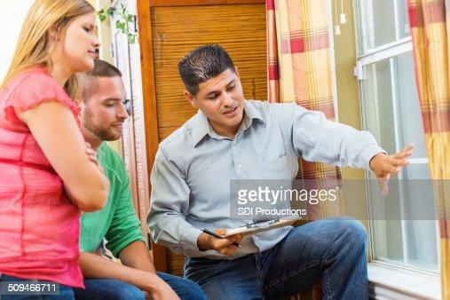 Home repairman explaining repairs to homeowners