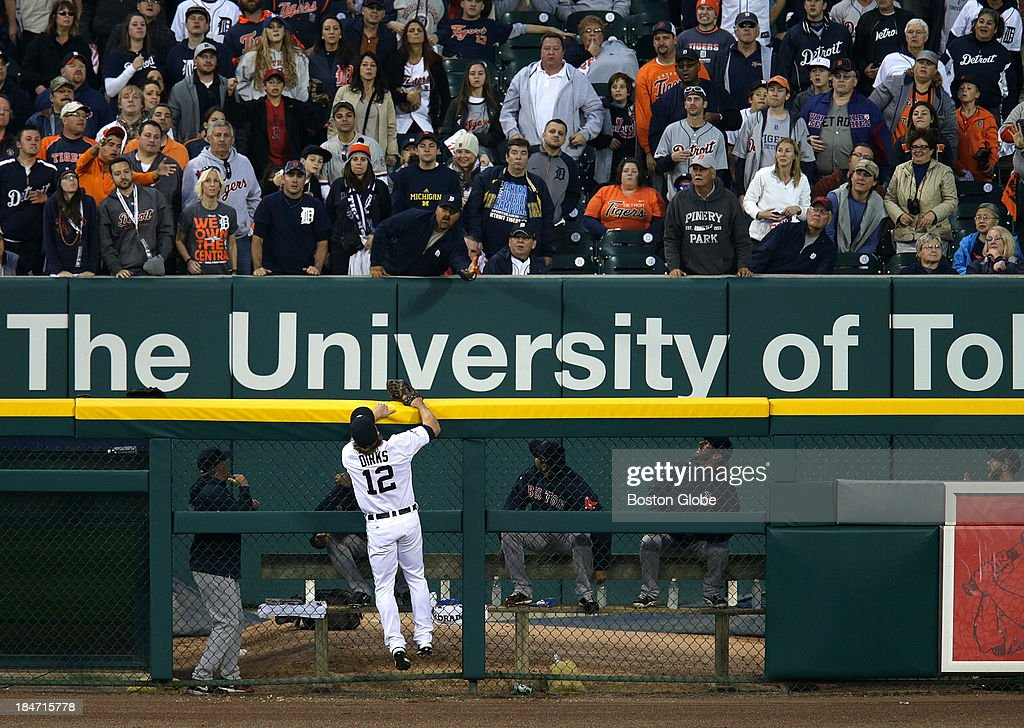 A home run ball by Boston Red Sox first baseman Mike Napoli (#12) is out of the reach of the fans and Detroit Tigers left fielder Andy Dirks (#12) as it lands in the Red Sox bull pen. The Boston Red Sox visited the Detroit Tigers in Game Three of the American League Champion Series at Comerica Park in Detroit, Mich., Oct. 15, 2013.
