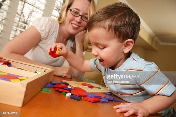 Home School Mom Helping Toddler Put Puzzle Together
