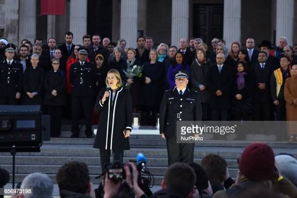Home Secretary Amber Rudd MP speaks as acting Commissioner of the Metropolitan Police Craig Mackey looks on during a candlelit vigil at Trafalgar...