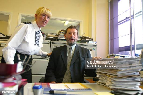 Home Secretary David Blunkett is shown a pile of police paperwork by Sergeant Anne Boothby during his visit to Chester Police Station in Cheshire *Mr...