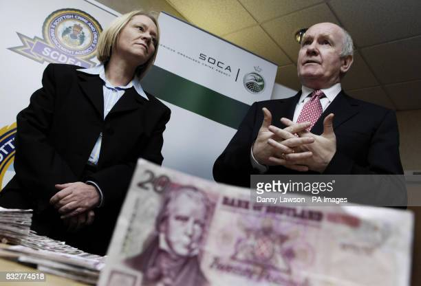Home Secretary John Reid and Scottish Minister for Justice Cathy Jamieson with a seized counterfeit note at the Scottish Crime and Drugs Enforcement...