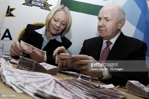 Home Secretary John Reid and Scottish Minister for Justice Cathy Jamieson with seized counterfeit notes at the Scottish Crime and Drugs Enforcement...