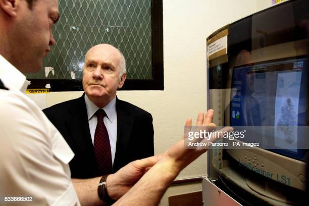Home Secretary John Reid is given a demonstration of LiveScan a new electronic fingerprint scanning technique by Sergeant Keith Edwards at Charing...