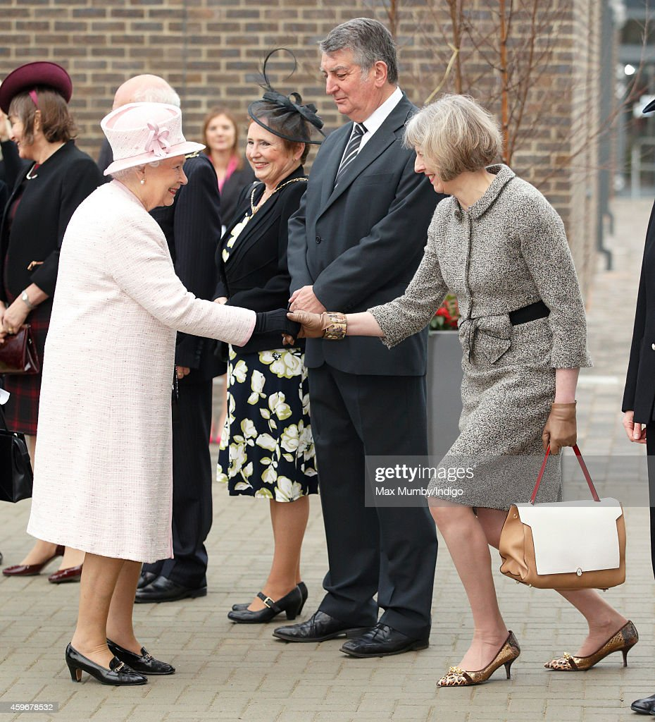 Home Secretary Theresa May curtseys to Queen Elizabeth II as she visits Holyport College on November 28, 2014 in Holyport, England.