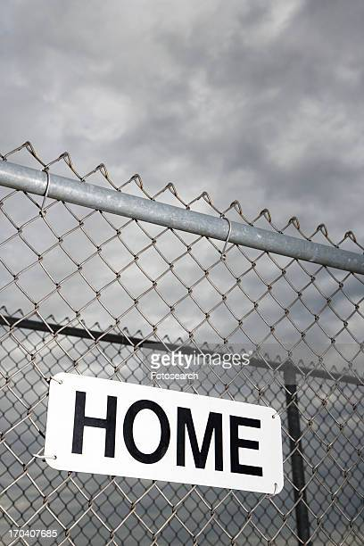 Home sign hanging on metal chain link fence