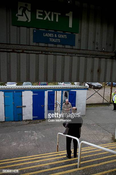 A home supporter enters the Popular Side of the ground through turnstiles at Barrow AFC's Furness Building Society Stadium prior to the delayed...