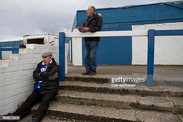 Home supporters waiting on the Popular Side terracing at Barrow AFC's Furness Building Society Stadium prior to the delayed kickoff of the Barrow v...