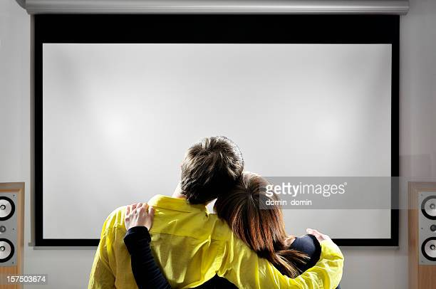 Home theater, hugging couple is watching movies on huge screen