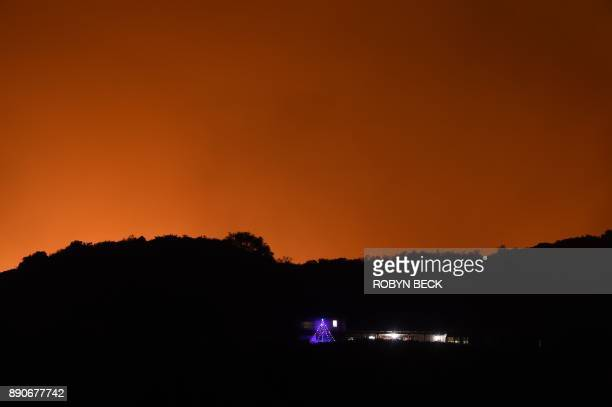 A home with a Christmas tree is seen in front of the orange night sky caused by the flames from the Thomas Fire in Montecito California east of Santa...