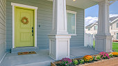 Home with porch and flowers in the garden. Exterior view of a home with colorful flowers in the garden and stairs going to the porch. The yellow front door is decorated with a simple wreath.