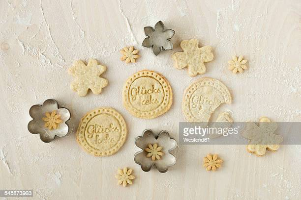 Home-baked fortune cookies and metal cookie cutters on light wood