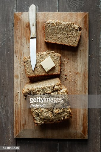 Home-baked glutenfree buckwheat bread, piece of butter and kitchen knife wooden board